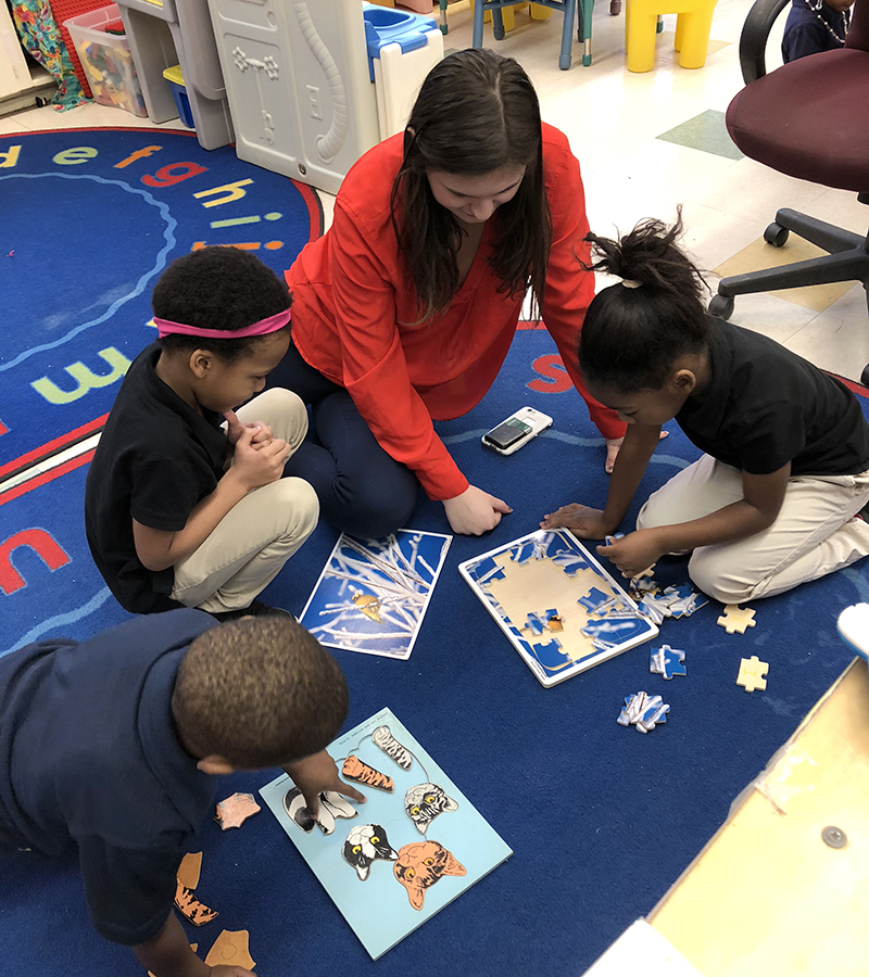 Katherine Klecha â18 assists students during creative time at Mariam Boyd Elementary School.