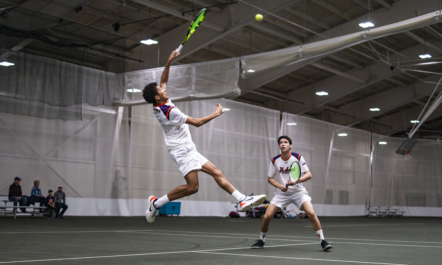 Jon Atwater '19 leaps for a volley during his doubles match with Thomas Shung '22 as Hobart defeats Oberlin College.