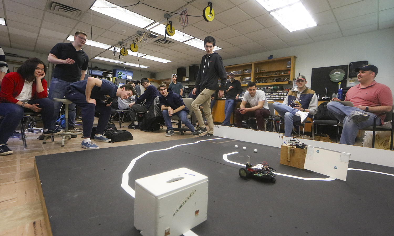 "Students watch their hand-crafted robots traverse an obstacle course as part of ""Robotics CS336""  with Professor of Mathematics and Computer Science John Vaughn P'08 (right) in Eaton Hall."