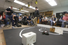 """Students watch their hand-crafted robots traverse an obstacle course as part of """"Robotics CS336""""  with Professor of Mathematics and Computer Science John Vaughn Pâ08 (right) in Eaton Hall."""