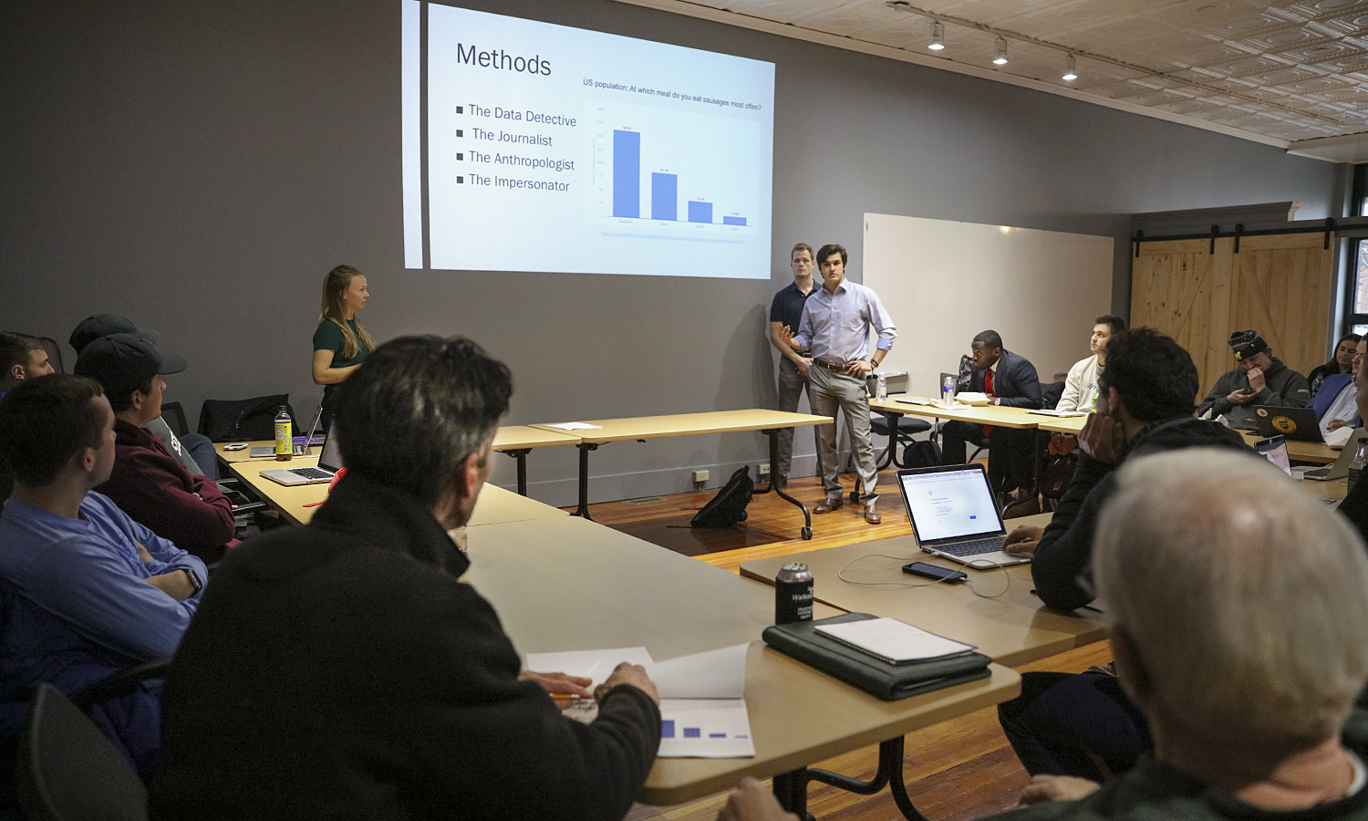 """Kelsi Carr 'X (left), Ben Grenier 'X and Riley McTeague 'X present their market research on Geneva to Richard Madia, owner of """"The Market"""", as part of their senior capstone course in the Bozzuto Center for Entrepreneurship at 22 Castle Street."""