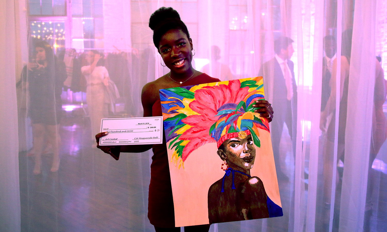 X stands with her prize winning photo during the annual Masquerade Ball hosted by the Carribbean Students Association at the Cracker Factory in Geneva, N.Y.