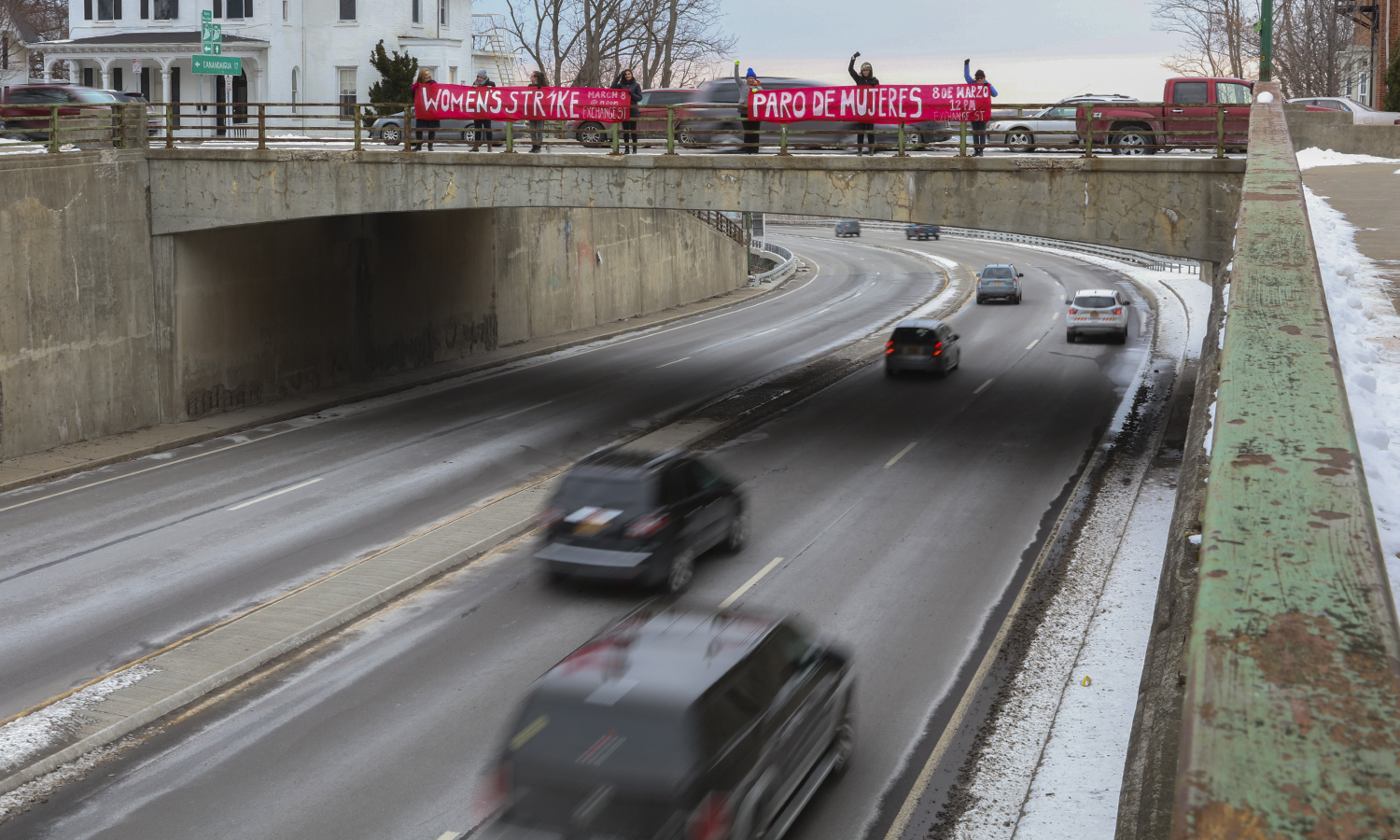 On Monday morning, members Geneva Women's Assembly held banners in English and Spanish over Route 5 and 20, announcing the March 8th International Women's Strike to Geneva commuters.