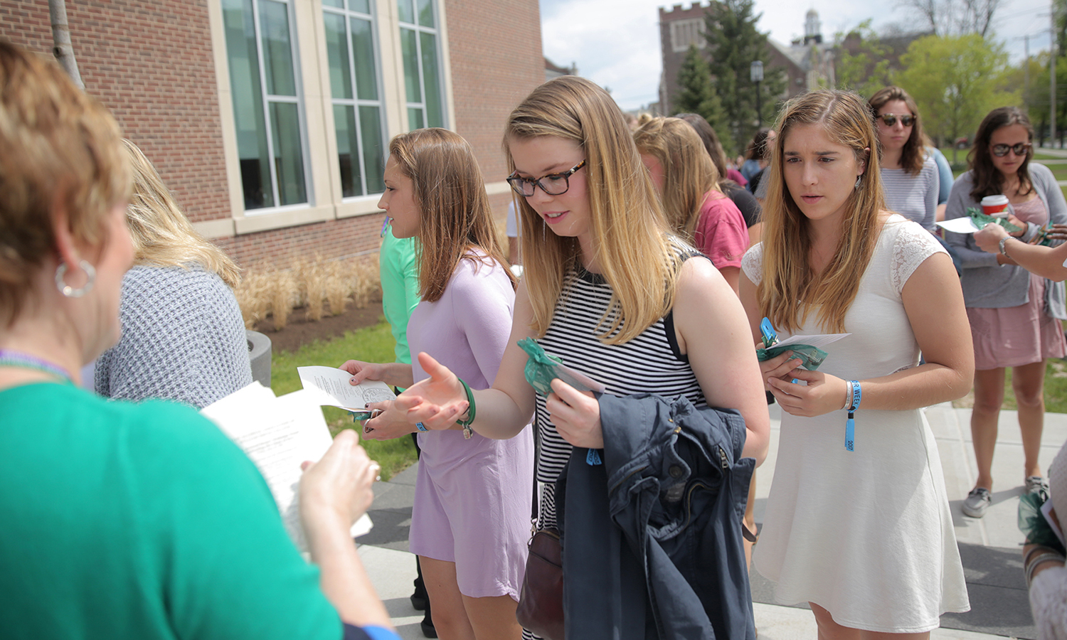 Emily Nason '17 and Stephnie Schmitz '17 receive a bracelet and the senior pine tree charm before the William Smith Senior Welcome Toast in the Gearan Center for the Performing Arts. The pine tree is in recognition of the College's nurseryman founder, William Smith.