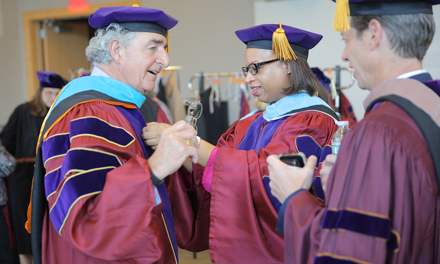 HWS Trustee Linda Arrington helps Chair of the Board of Trustees Thomas S. Bozzuto '68 during robing for Sunday's Commencement ceremony.