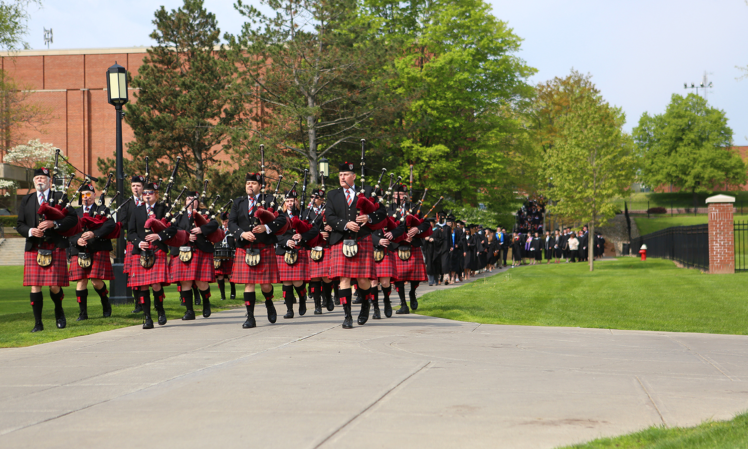 The Mohawk Valley Frasers Pipe Band leads the Commencement procession.