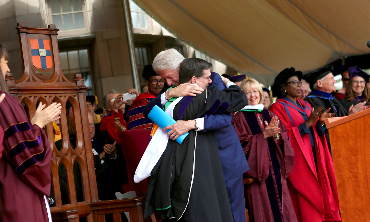 President Mark D. Gearan and President Bill Clinton hug each other during Commencement 2017.