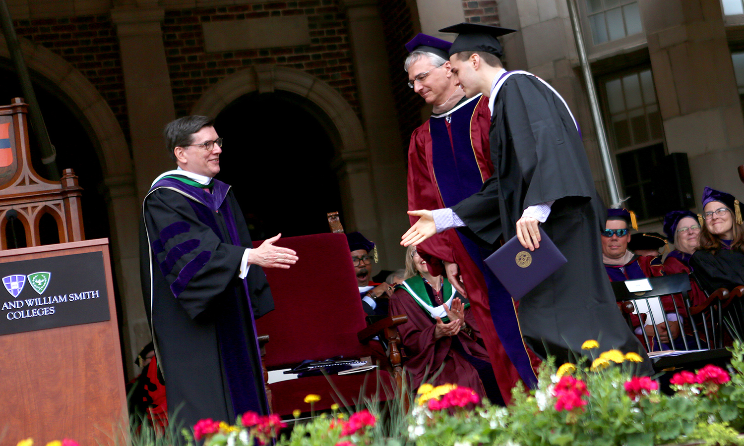 Joined by his father Craig Stine '81 P'17, Jack Stine '17 (right) accepts his diploma from President Mark D. Gearan during Commencement.
