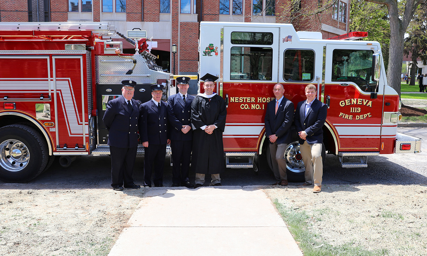 Volunteer firefighter John Hillenbrand '17 poses for a photo with members of the Nester Hose Company following the Commencement Ceremony on Sunday.