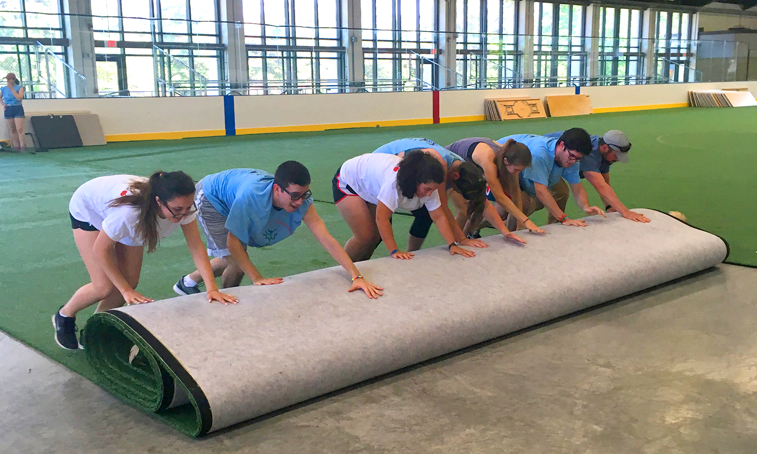 "Students help roll out artificial turf in ""The Cooler"" in preparation for the annual Community sale."