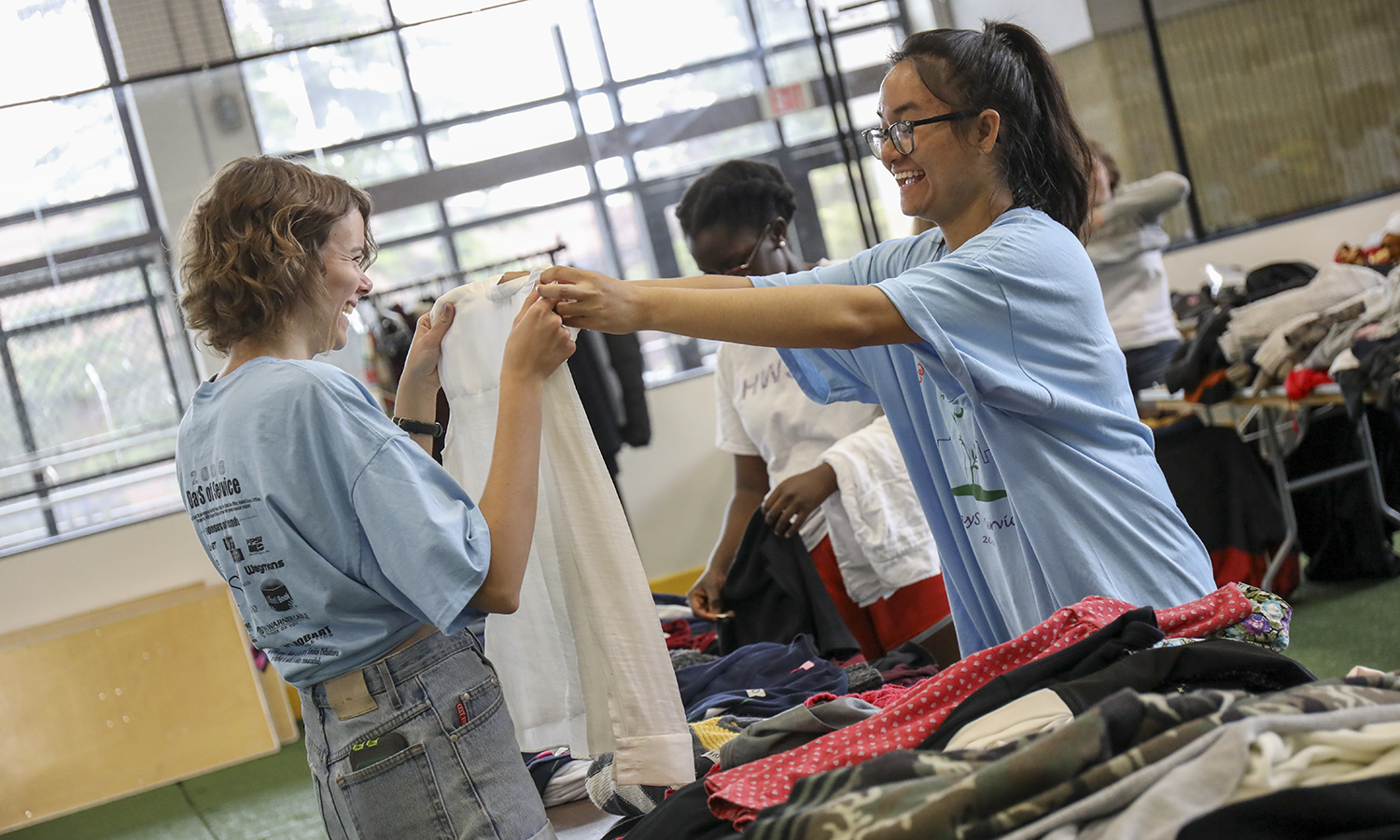 Ren Workman '18 and Swellar Zhou '18 fold shirts at the Community Sale in the Geneva Recreation Center.