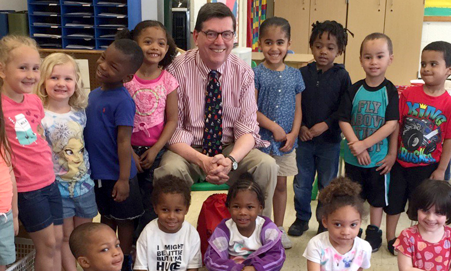 Local elementary students participating in the Geneva Head Start program pose for a photo with Mark D. Gearan.