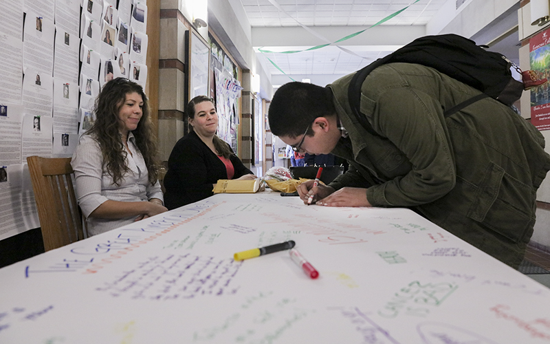 Brittany Broderick and Shells Basilio from Res Ed watch Carlos Robles '18 sign a banner with reasons for not smooking as part of the Great American Smoke Out.