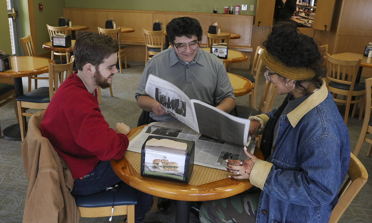 James Monaco '20, Kevin Cervantes '21 and Divya Tewari' 20 discuss current events while reading <i>The New York Times</i> in the Scandling Campus Center.