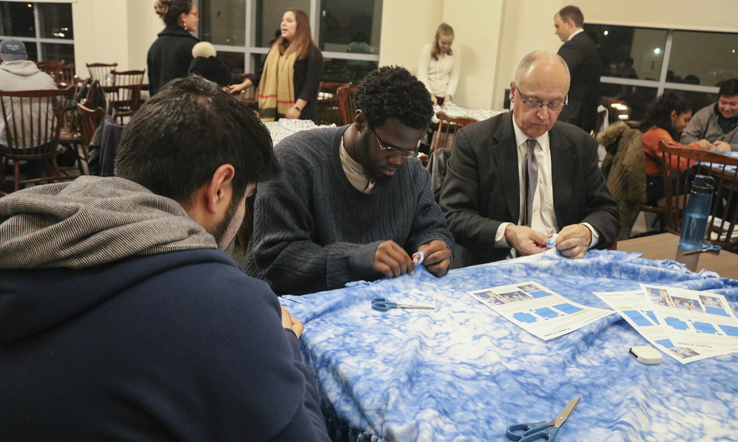 Director of Campus Safety Marty Corbett (right) and Jedidiah Collins 'xx create no-sew scarves and blankets for local refugees in the Scandling Campus Center Common Room.