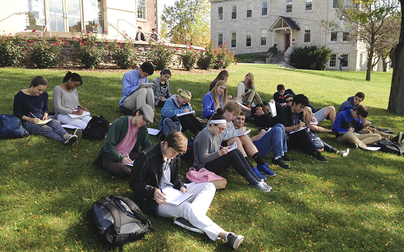Students in Assistant Professor of Geoscience Nick Metz's First-Year Seminar on Climate Change: Science and Politics take advantage of the beautiful weather to hold class outdoors.