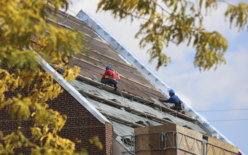Workers add the slate shingles to the new Performing Arts Center on a beautiful Fall day. The center is on track to be opened in January 2016.