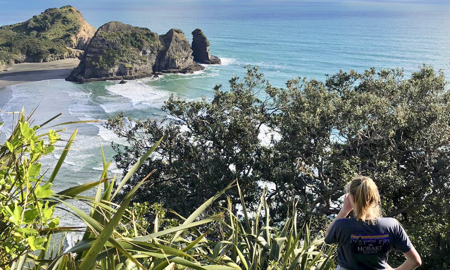Colleen McGowan '20 poses for a photo on the top of Lion Rock along Piha Beach while studying abroad in New Zealand.