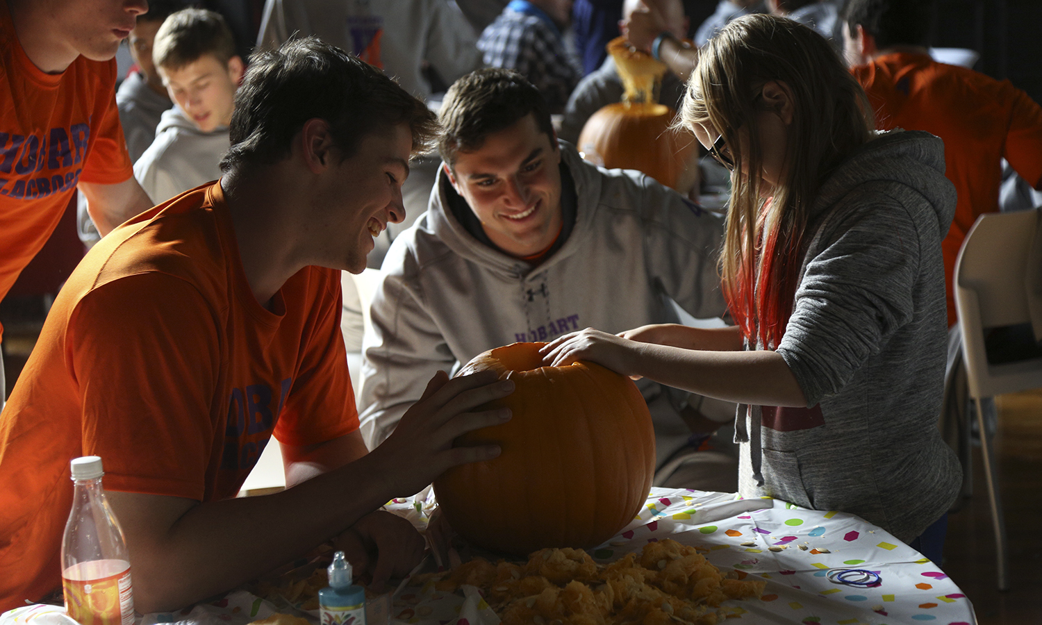 Tristan Doherty '19 and KoKo Avedisian '19 carve pumpkins with students from the Boys and Girls Club in Bartlett Theatre.