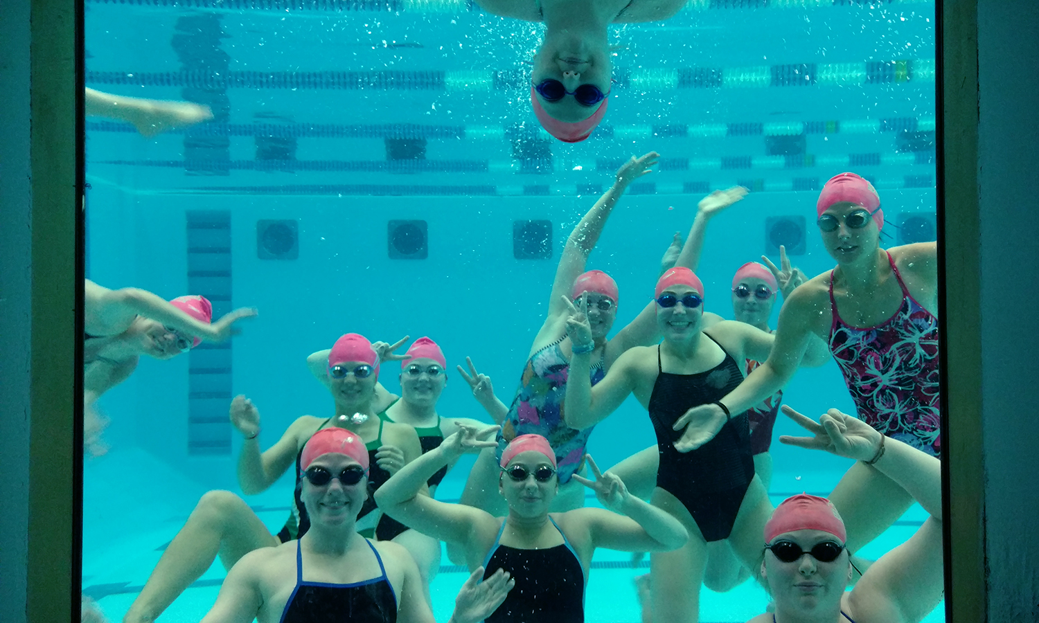 Members of the William Smith Swimming and Diving team wear pink swim caps during practice to show their support of breast cancer awareness month.