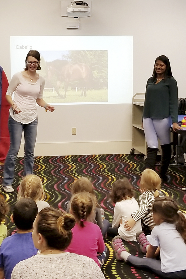 "As part of ""Topics in Bilingual Education"" with Associate Professor of Spanish and Hispanic Studies May Farnsworth, Jane Lawrence '21 and Selena Kattick '20 teach in Spanish to children at the Geneva Public Library."