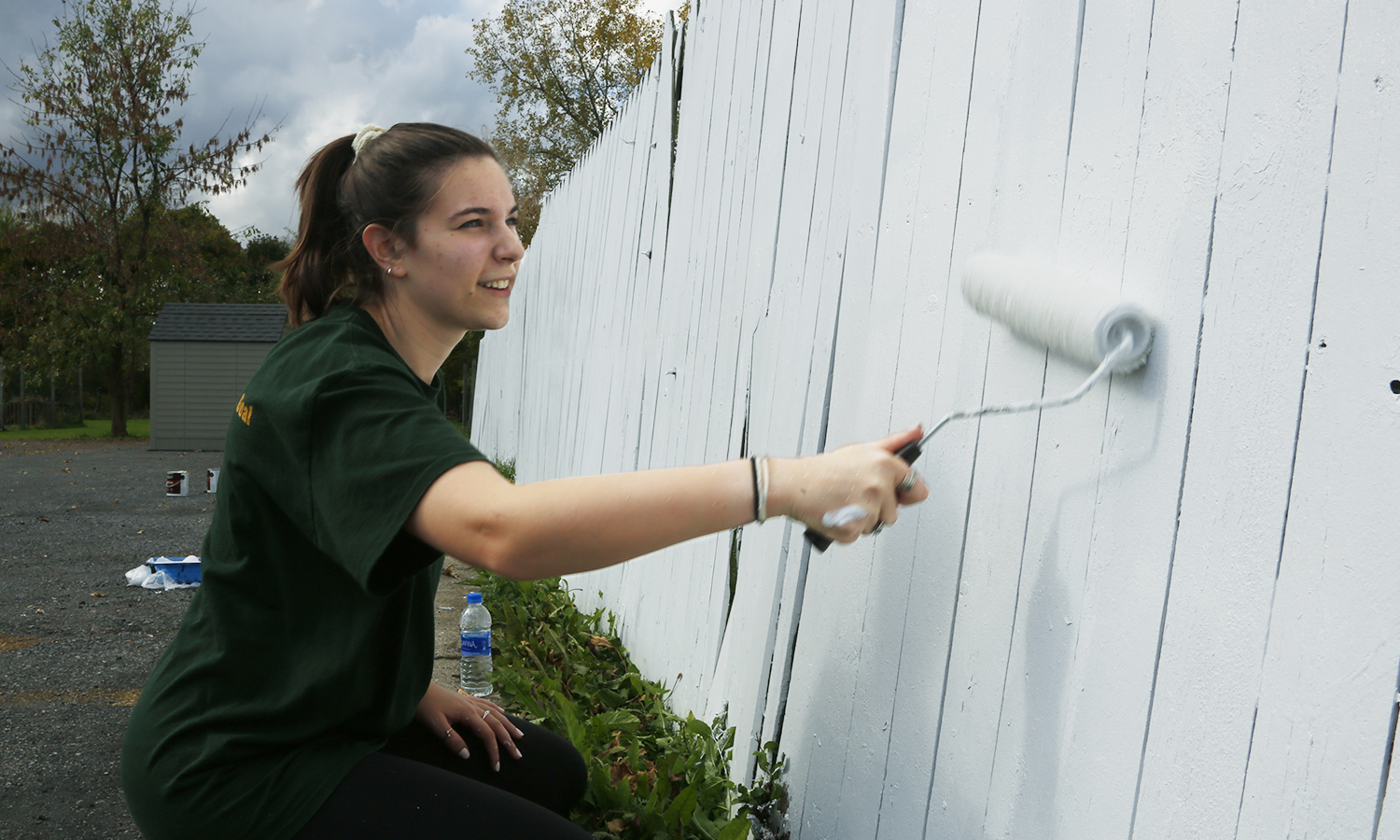 Tessa Englander 'X paints a fence at Mt Olive Missionary Baptist Church.