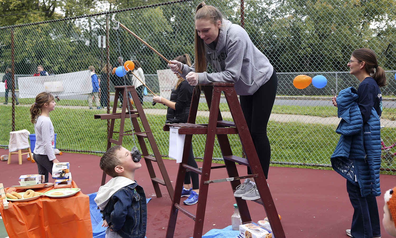 Charlotte Engebrecht â21 entertains community memebers with the âdonut on a stringâ game during the Hildreth Hill Pumpkin Roll.