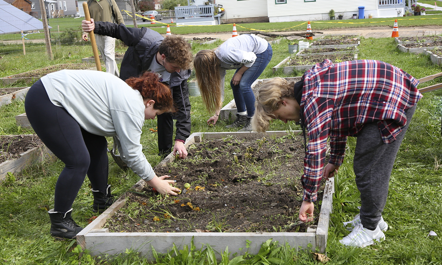 Students help clean up gardening boxes at X.
