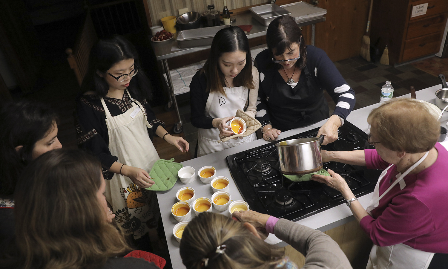"Renowned Kosher chef, food scholar and author Tina Wasserman helps students pour homemade caramel into ramikins as part of ""Cooking, Culture and Chemistry."""