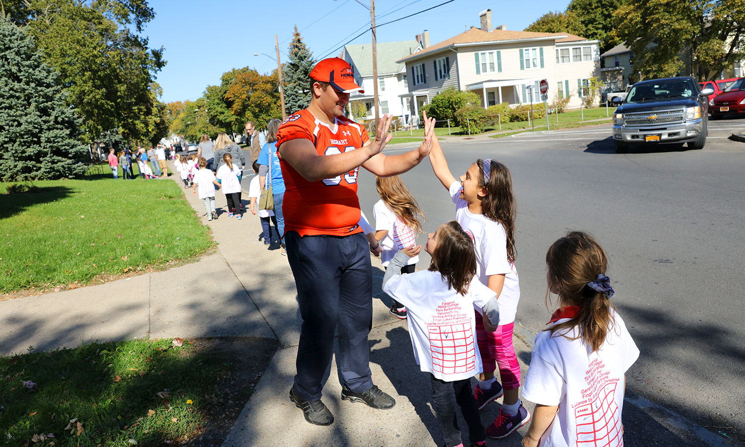 Hobart football player Colin Smith 'X high fives students as they complete their laps for the Walk-A-Thon.