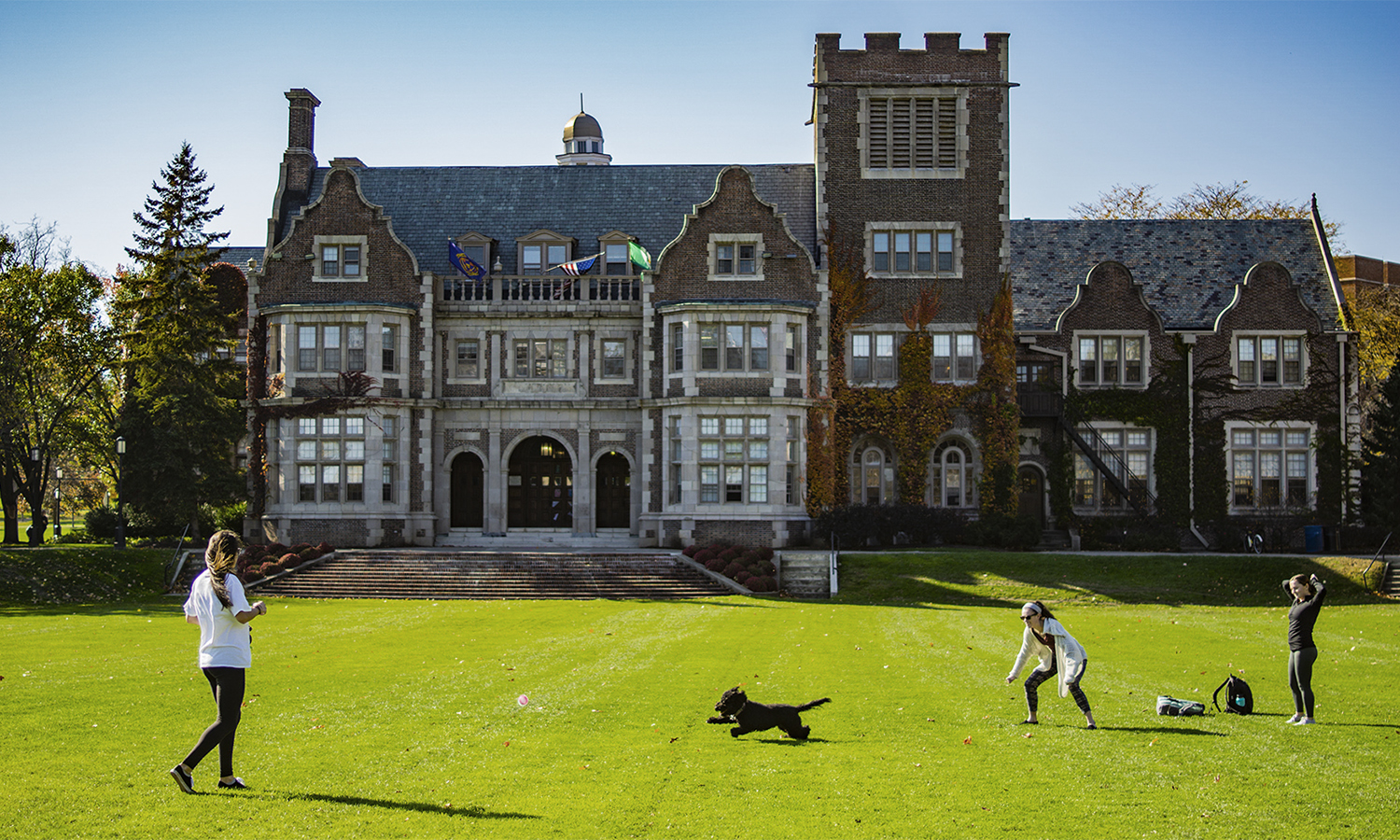 Liza Alexakos '20, Lily Shea '20, and Hadley Browning '20 play fetch with their dog Bea on the Quad.
