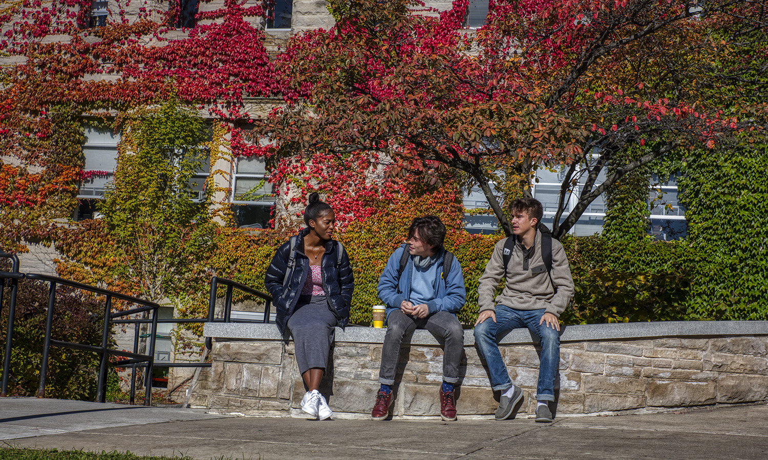 Krysten Palmer '22, Austin Kennie '19 and Kyle Driscoll '22 chat outside of Demarest Hall.