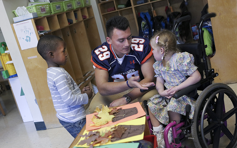 Hobart Football visit to Happiness House in Geneva. #29 Junior Austin Gallegos