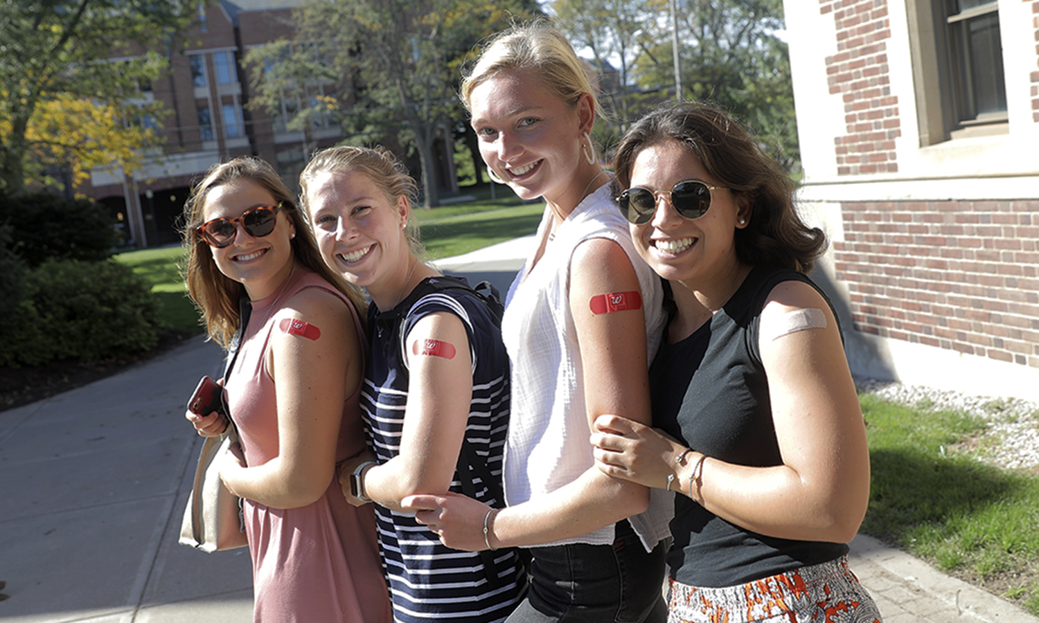 Christine Moloney '17, Maya Weber '20, Cailin Gensler '21 and Audrey Morin '21 pose for a photo after receiving their flu shots on campus.
