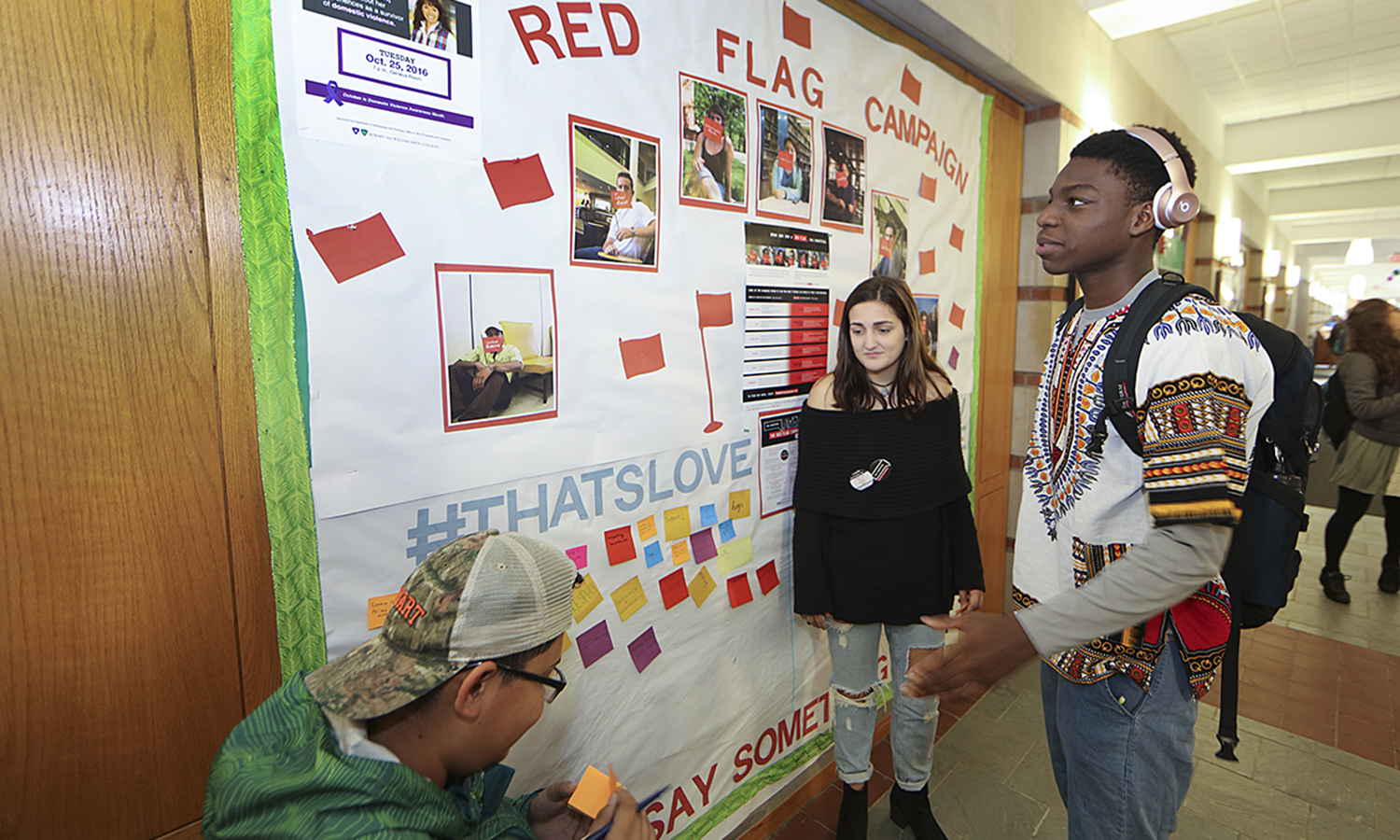 Maria Moreau '19, Henry Castillo '20 and Israel Oyedapo '20 encourage students in Scandlng Campus Center to write a message educating, empowering and activating the community to recognize unhealthy relationships through the One Love Foundation.