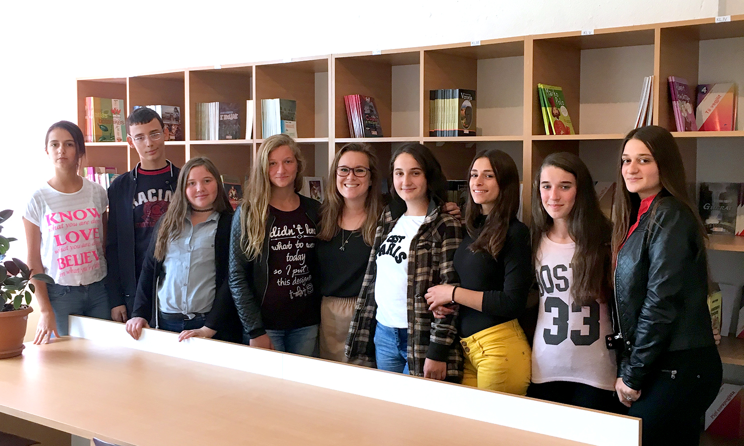Emily Surprenant '15 (middle) with her English students in Kosovo, where she is a Peace Corps volunteer, stand in front of their brand new library. Surprenant wrote several grant applications in order to transform a vacant classroom into a functioning library for her students, complete with over 1000 books.