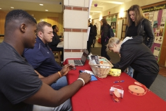 Hobart football players Micah Holloway '19 and Patrick O'Connell '17 talk to Rebecca Via '19 and Amanda Breed '19 about how they can support Happiness House, an organization that provides programs and services to people with disabilities and their families in the nearby area.