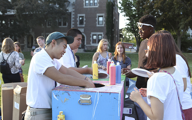 Orientation Mentors Jason Kwong '18 (front) and Carlos Robles '18 (back) help First Year students paint frisbees.