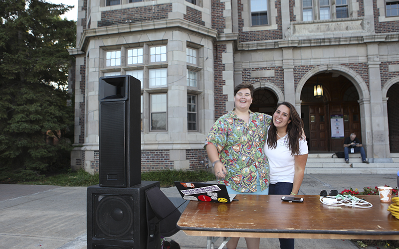 Seniors Virginia Dewees (check spelling) and Lucia Cardone work the music while First Years enjoy dinner and bounce houses on the Quad.