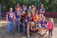 Members of the Hobart football team gather for a photo with students from Happiness House.