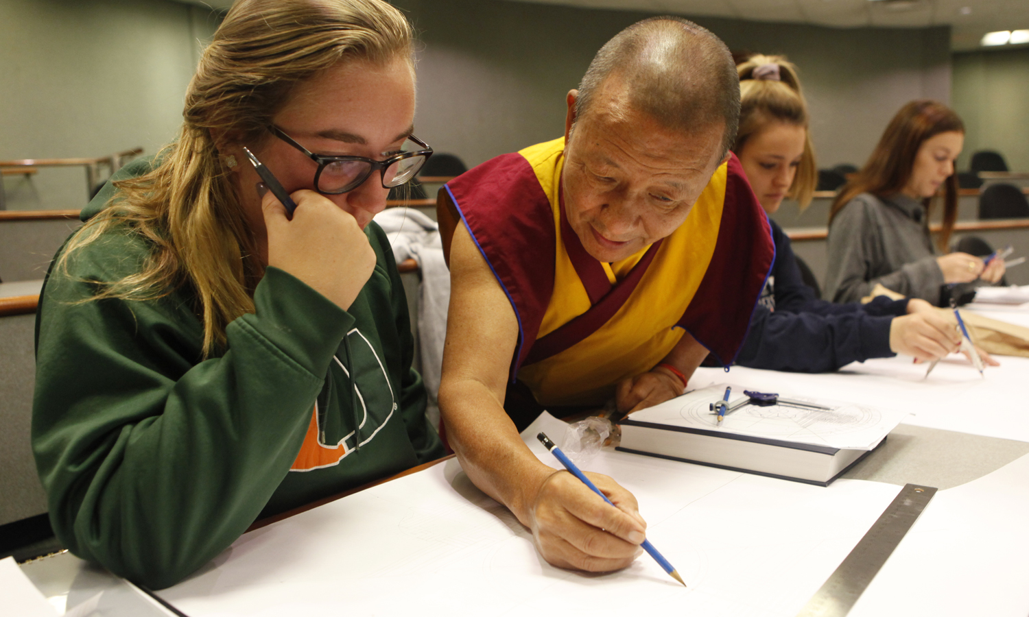 "Brice Winder 'X gets a helping hand from the The Venerable Tenzin Yignyen during ""Tibetan Mandala Painting,"" in the Sanford Room in Warren Hunting Smith Library."