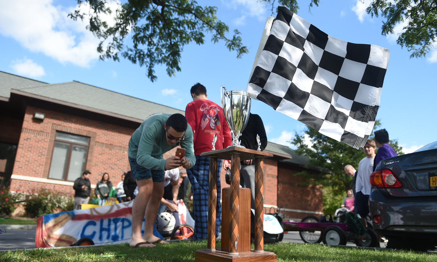 Jake Mirsky 'X snaps a photo of the trophy before Fall Nationals on Saturday of Homecoming and Family Weekend.