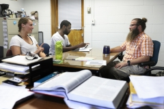 Briana Curran '19 and Vernon Lawson '16 meet with Josh Newby, Assistant Professor of Chemistry in his office.