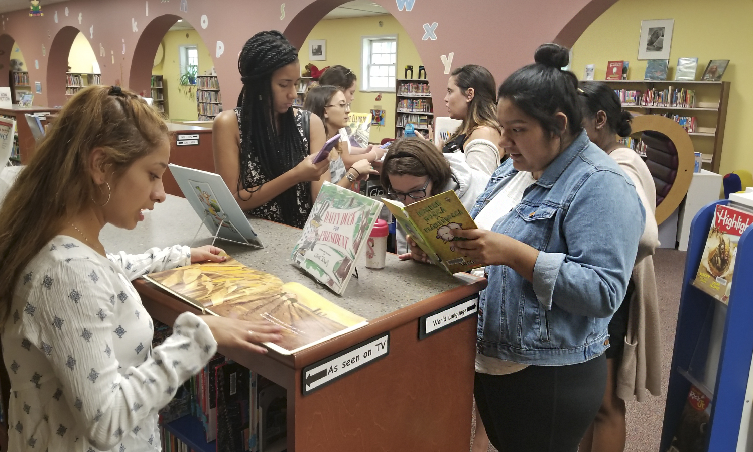 "​Students in ""Topics in Bilingual Education"" with Associate Professor of Spanish and Hispanic Studies May Farnsworth review Spanish-language books for children at the Geneva Public Library."