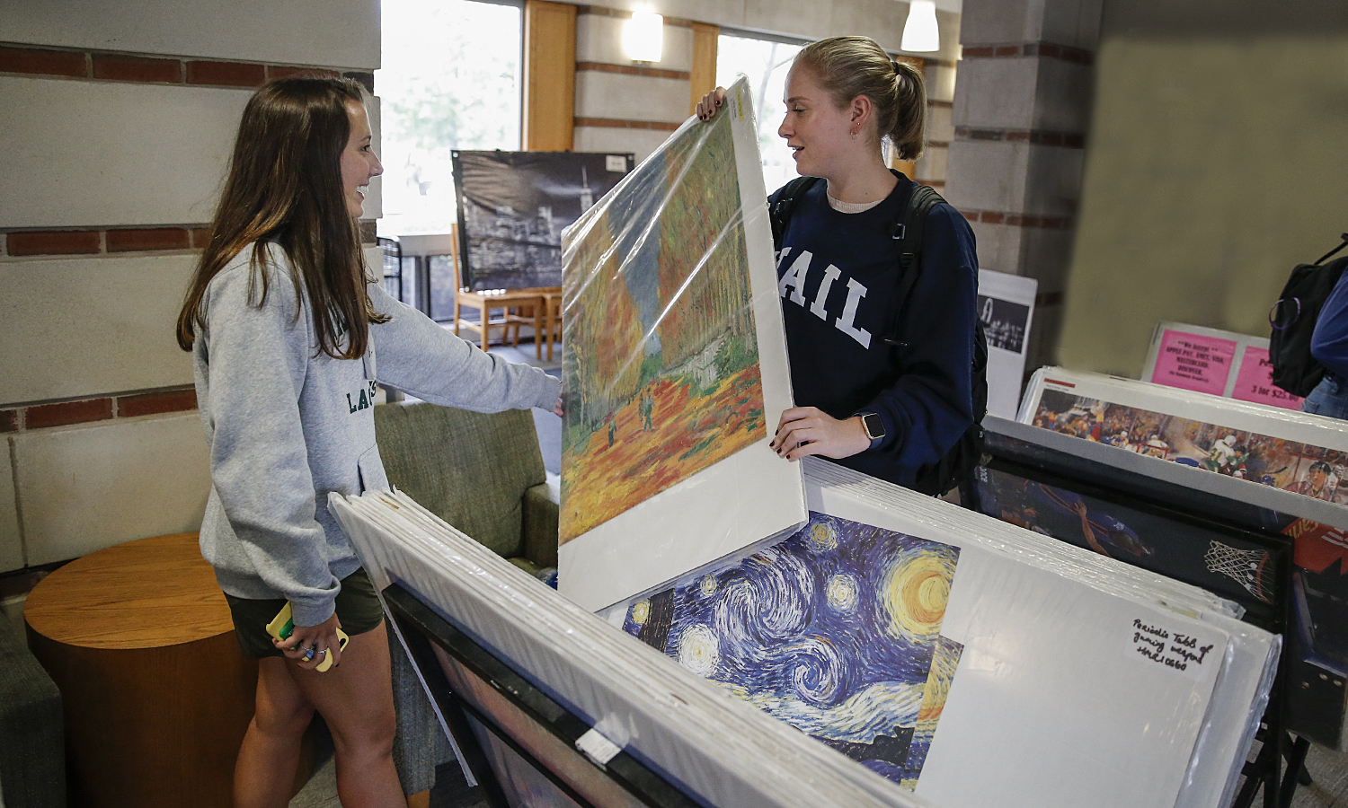 Sadie Mapstone '21 (left) and Emma Levensohn '21 check out a poster of a painting by Vinent Van Gogh during the annual poster sale in the Scandling Campus Center.