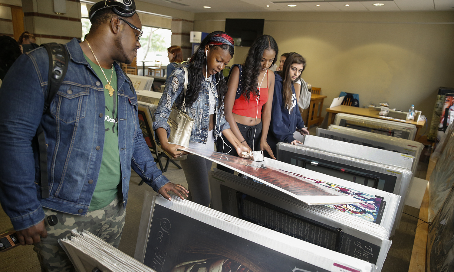 Students browse through posters in the Scandling Campus Center during the annual poster sale on campus.