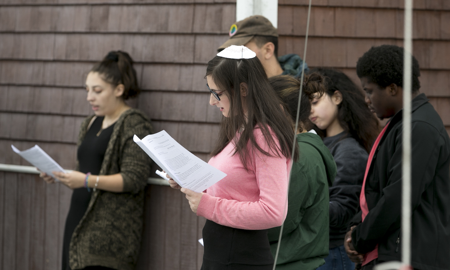 Emme Hauck '21 (left), Natalie Miggins '22, Gizem Hussain 'X and Christopher Bell '19 participate in the Rosh Hashanah​ service on the dock  of Bozzuto Boathouse.