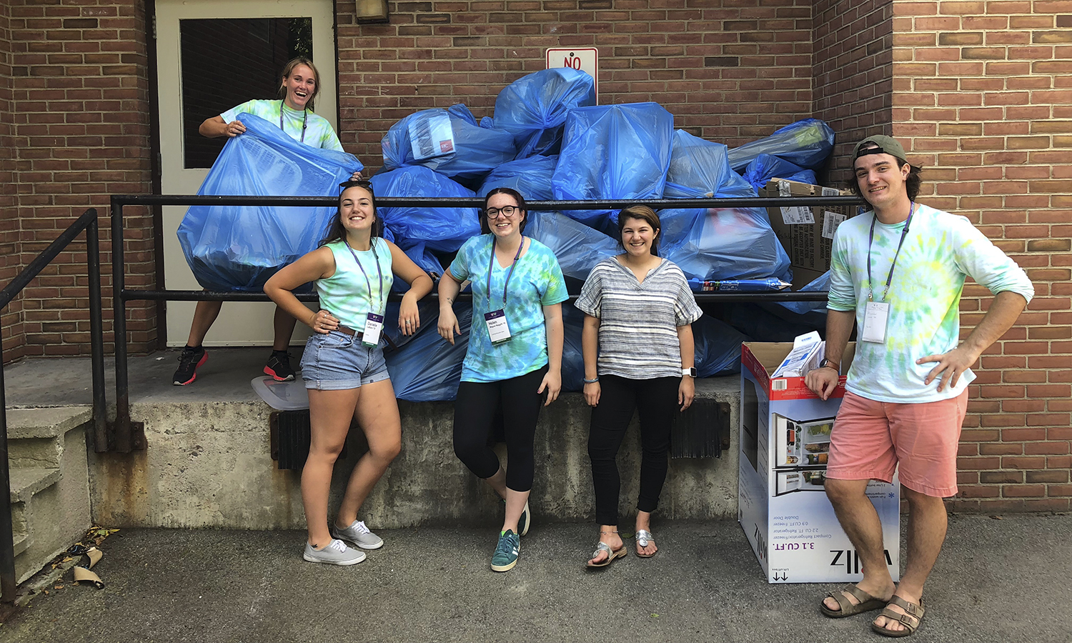 HWS EcoReps stand in front of a mound of blue bags, filled with recyclables, mostly cardboard from FYs moving into JPR.