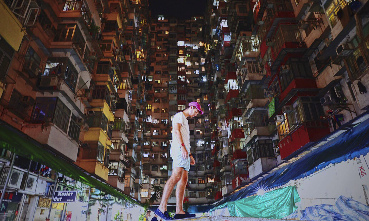 Jonah Salita 'X walks along a dividing wall in downtown Hong Kong.