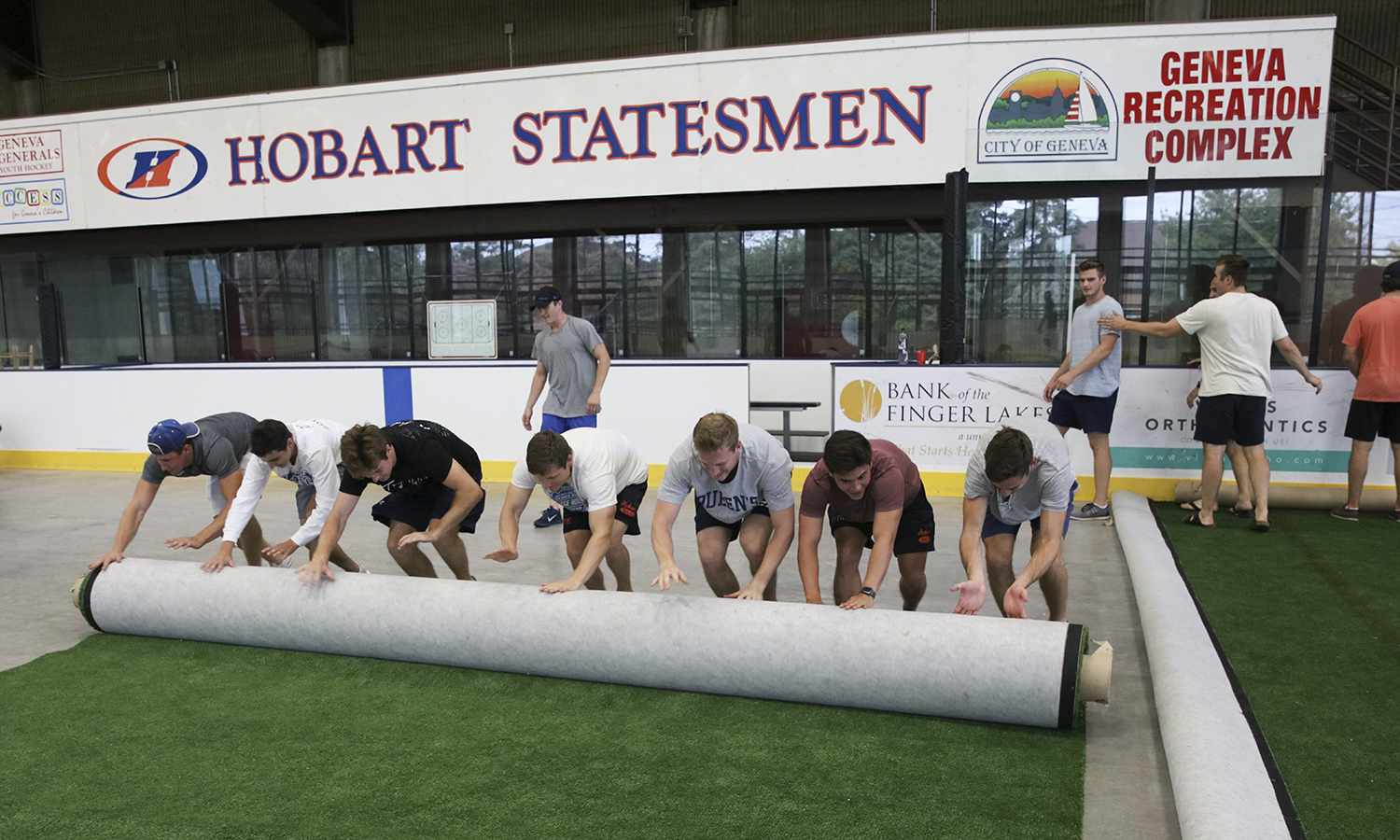 Members of the Hobart Hockey Team roll up turf at the Cooler.